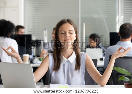 Mindful millennial girl meditating in office taking break for meditation at work, young woman managing stress practicing yoga at workplace for mental emotional balance, no stress free relief concept
