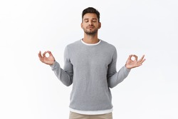 Mindful patient and relaxed young happy man, practice breathing exercises, hold hands sideways and smiling relieved, release stress during work time take break to meditate, white background
