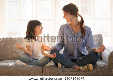 Mindful young mom teaching yoga happy cute funny child daughter sitting in lotus pose on couch together, smiling mother and little kid girl meditating relaxing at home, healthy family exercises