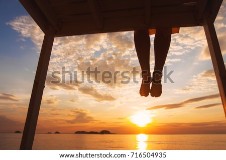 mindfulness concept, woman enjoying summer evening on the beach at sunset, silhouette of feet of happy girl sitting alone on the pier