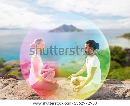 mindfulness, spirituality and outdoor yoga - couple meditating in lotus pose with rainbow aura over seychelles nature background
