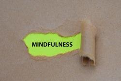 Mindfulness  word written under torn paper. Mindfulness ,  concept Image.