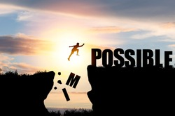 Mindset concept ,Silhouette man jumping over impossible and possible  wording on cliff with cloud sky and sunlight.