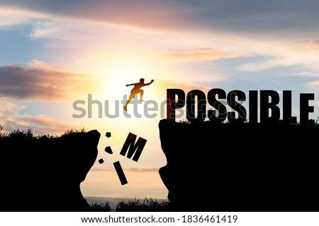 Mindset concept ,Silhouette man jumping over impossible and possible  wording on cliff with cloud sky and sunlight. Stock fotó ©