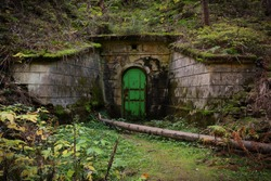 Mine entrance. Unesco heritage Ore mountains mines. Czech Republic, Krusne hory. Underground metal doors in forest. Abandoned mine. Stone building in forest. Mysterious forest place.