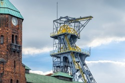 Mine shaft tower and historical clock tower in coal mine 'Wieczorek' in Katowice, Silesia, Poland.