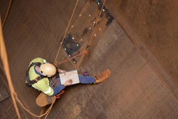 Miner rope access engineer planer  working at height abseiling into the chute,  writing, drawing defected, faulty, damage liners his planing book during shut down operation Sydney mite site, Australia