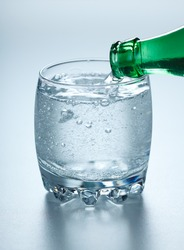 Mineral water being poured into glass from green bottle