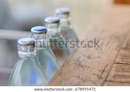 Mineral water glass bottle line with droplets near wooden table (Copy Space, Selective focus, One concept) #678991471