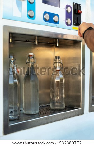 Mineral Water machine on the street. Filling mineral water bottles from a water dispenser. Pay and load drinking water.