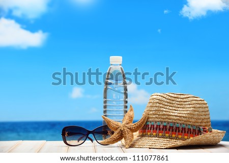 Mineral water,straw hat and sunglasses on beach table.