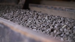 Minerals moving on conveyor belt in factory. Stock footage. Crushing and processing plant of minerals. Stone ore on conveyor plant factory