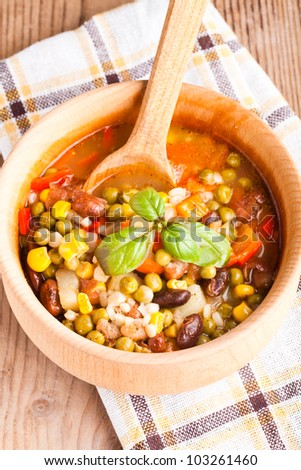 Minestrone soup in wooden bowl closeup. Traditional italian dish