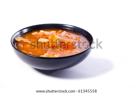 Minestrone, the Italian vegetable soup, in a black bowl. Isolated on white.