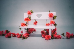 mini baby bench with pink flowers in a photo studio