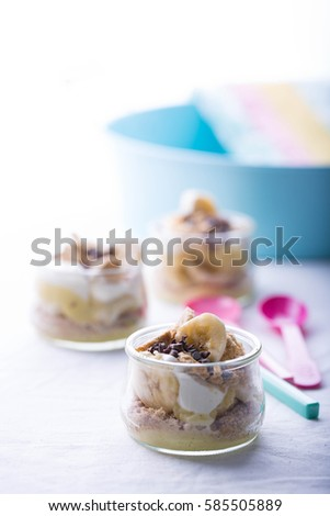 Mini banana and vanila pudding trifle in a glass jar.  #585505889