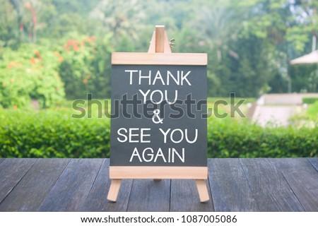 Mini blackboard written thank you and see you again over blurred background
