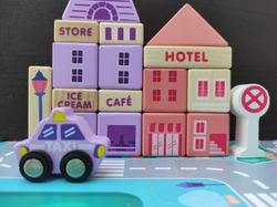 Mini Blocks Discribe Hotel With Cafe Store Beside And A Taxi In The Front With Black Wooden Background