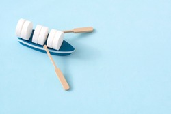 mini boat carrying pills on yellow background. Transportation and delivery of medicines