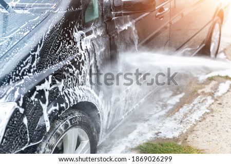 Mini bus van car wash with high pressure water equipment pump at home backyard outdoors on bright shiny summer day. Vehicle covered with foam shampoo chemical detergents during carwash self service Stock photo ©