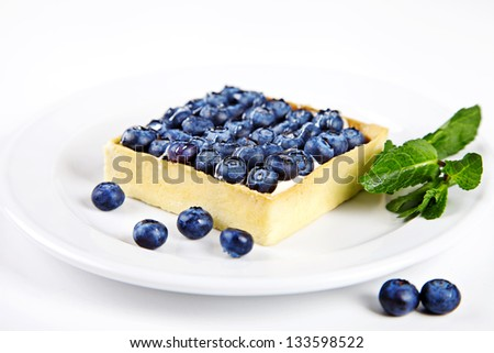 Mini cake with blueberries and mint on white background