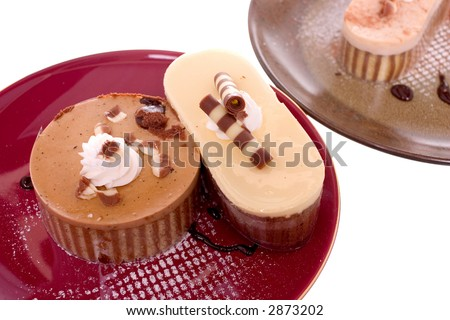 mini cakes and mousses on dessert plates, on white ground