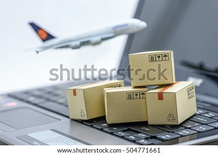 Mini cardboard boxes on a laptop with a plane flies behind. For several purposes or ideas about transportation, international freight, global shipping, overseas trade, regional  / local forwarding.