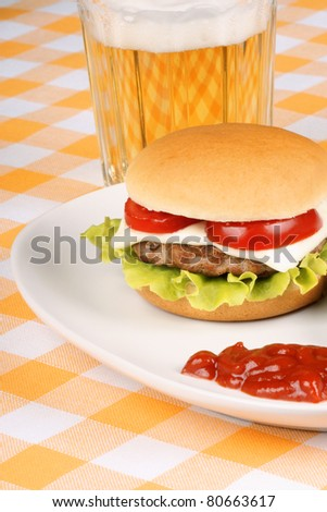 Mini cheese burger with tomato and lettuce on a white dish and a glass of beer.