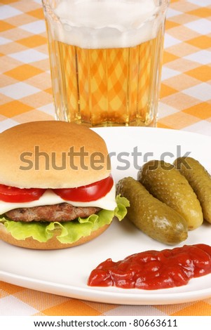 Mini cheese burger with tomato and lettuce, some pickles and ketchup on a white dish and a glass of beer.