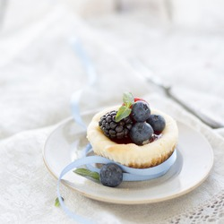 Mini Cheesecake with Raspberries Blackberries Blueberries Mint Leaves on Small Plate Blue Ribbon on Lace Napkin Old Table Top Rustic Style.