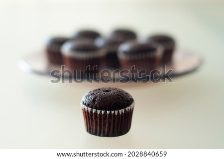 Mini chocolate muffins in a plate on glass table. Homemade mini brownie cupcakes on desk or kitchen counter. Mini cakes in paper forms. Blurred background.