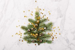 Mini Christmas tree made of fir branch on marble background. New Year concept. Flat lay.