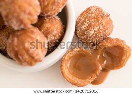 Mini Churros filled with dulce de leche (milk caramel)  on white background. Selective focus. #1420912016