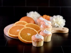 Mini Creamsicle cupcake with orange and white frosting and fresh orange slices arranged on a wooden cutting board with white and orange flowers in the background on a black subway tile!