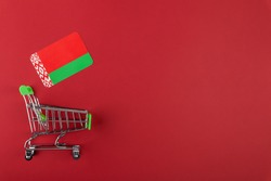 Mini empty supermarket shopping grocery cart, Belarus flag on red background