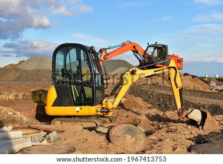 Mini excavator during earthmoving at construction site. Backhoe dig ground for the construction of foundation and laying sewer pipes district heating. Earth-moving heavy equipment on road works ストックフォト ©