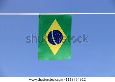 Mini fabric rail flag of Brazil, a blue disc depicting a starry sky with the national motto Order and Progress, within a yellow rhombus, on a green field. It hanging on the rope cloth on blue sky. #1119764612