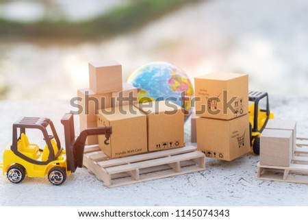 Mini forklift truck load stack of cardboard boxes with shopping cart symbol on wooden pallet and globe near by. Logistics and transportation management ideas and Industry business commercial concept.