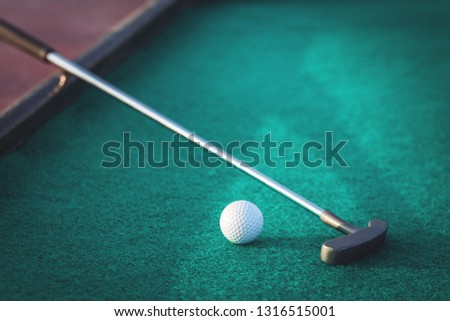 Mini golf two-way putter club and a ball on green surface close up with copy space