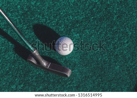 Mini golf two-way putter club and a ball on green surface with copy space
