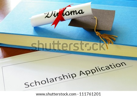 mini graduation mortar board and diploma with scholarship application