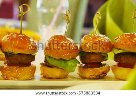 mini hamburger with salad leaf served on the plate on restaurant table