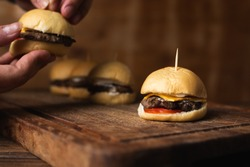 Mini homemade burger with cheddar cheese, tomato and mayonnaise to eat them as snacks. Hands grabbing a burger in the background. Horizontal image with space for text.