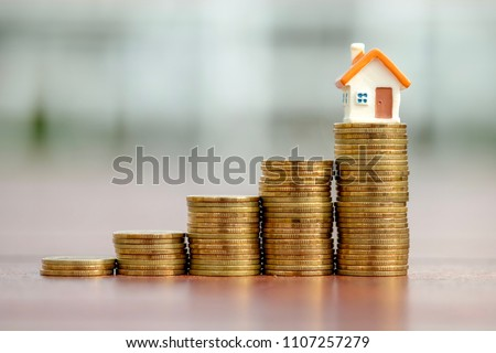 Mini house model on top of growth stack of coins. Saving money for property investment. Business and finance concept