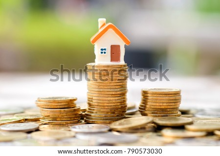 Mini house on stack of coins. Business and finance concept.