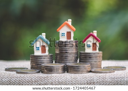 Mini house on stack of coins, Concept of Investment property, Investment risk and uncertainty in the real estate housing market.