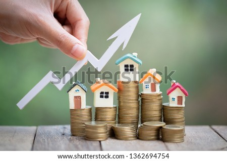 Mini model house on coins stack, growing business, Property investment and house mortgage financial concept