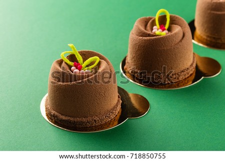 Mini mousse pastry dessert covered with chocolate velour on green background. Modern european cake. French cuisine