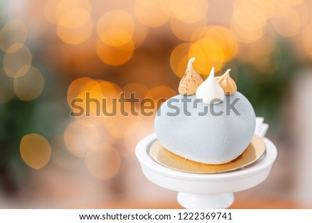 Mini mousse pastry dessert with gray velour on garland lamps bokeh background. Modern european cake. French cuisine. Christmas theme