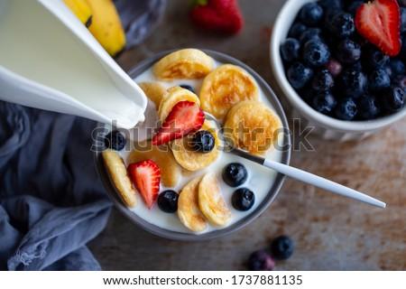 Mini oatmeal pancakes. pancakes with blueberries and strawberries.Pancake porridge, mini pancakes in a bowl with milk and maple syrup.Dutch mini. Milk is poured onto mini pancakes.kids' food.Milk day.